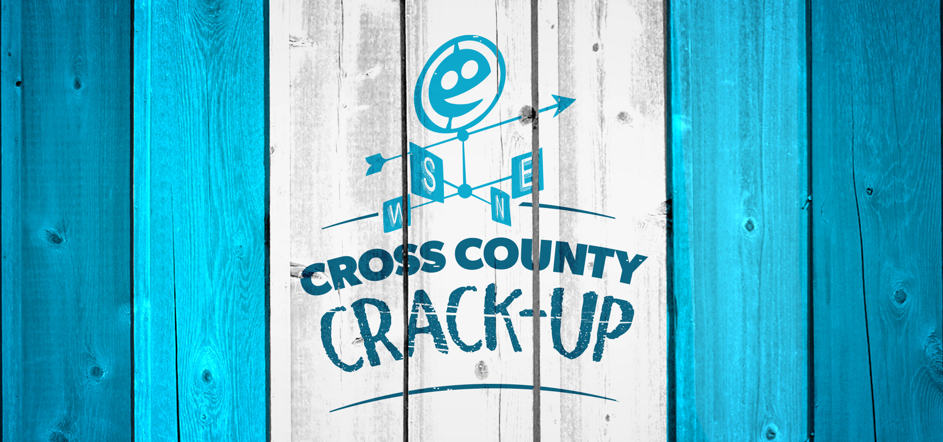 Image Description: Barn boards painted tonal blues and white featuring a logo treatment for Cross County Crack-up including a stylized happy face and a weather vain.