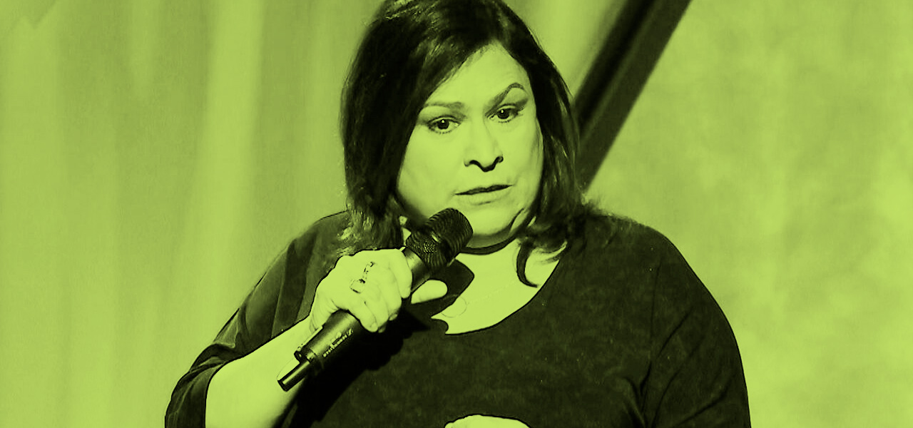 Image Description: A green filtered photograph of Martha Chaves in the midst of a stand-up comedy set.